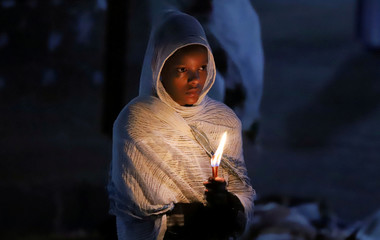 An Ethiopian Orthodox faithful holds candles during the Easter eve prayers at the Holy Trinity Cathedral Orthodox church in Addis Ababa