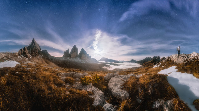 Panarama Mountain valley at beautiful night. Autumn landscape with mountains, hills, stones, grass, blue sky with clouds and moon at sunset. High rocks at dusk. Tre Cime park in Dolomites, Italy.