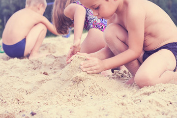 Group of little cute childs makes sand castle at the beach