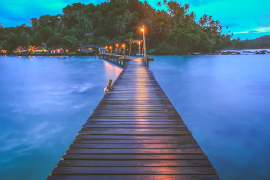 View of wooden bridge extending to the  the beach at twilight in tropical island