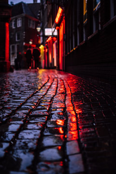 Red ligths of a famous red light distict in Amsterdam, Netherlands. Reflection of neon lighting of showcase windows over wet pavement. European capital of legalized prostitution and marijuana.