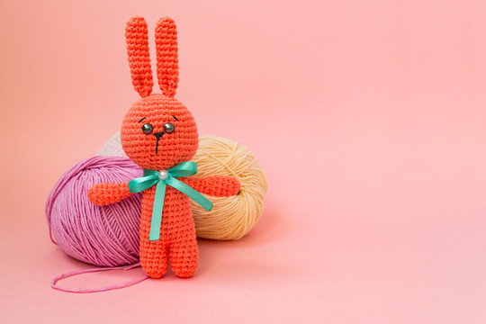 Orange knitted hare stands on the background of multi-colored balls of yarn on a pink background. There is a place for text.