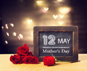 12 May Mothers day message on a small chalkboard with red roses