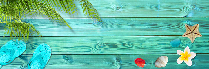 Palm leaf, flip flops and seashells on blue wooden planks, panoramic beach and summer background with copy space