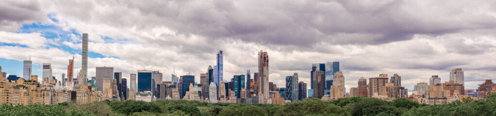 The beautiful New York City skyline with an interesting cloudy sky behind. Panorama of full skyline with all the famous towers and buildings. Wall mural