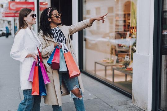 Two beautiful women enjoying shopping and choosing what to buy together