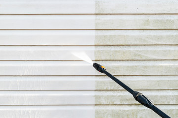 Cleaning service washing building facade with pressure water. Cleaning dirty wall with high pressure water jet. Power washing the wall. Cleaning the facade of the house. Before and after washing