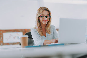 Cheerful young woman smiling while using laptop at work