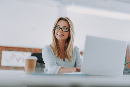 Positive businesswoman sitting with laptop and looking away