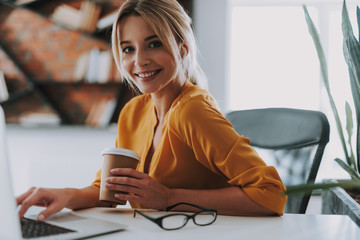 Woman in orange blouse having cup of coffee and laptop on the table