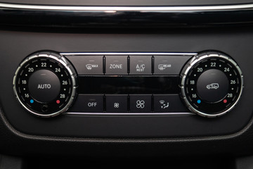 Rear central console on the panel inside the car close-up with climate control and seat heater buttons in gray and black. Auto service industry. Comfort concept.