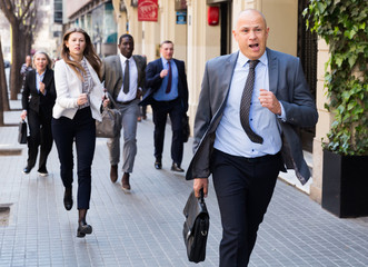 Hurrying people with stressed man in foreground