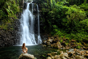 Young woman in bikini sitting by Middle Tavoro Waterfalls in Bouma National Heritage Park, Taveuni Island, Fiji