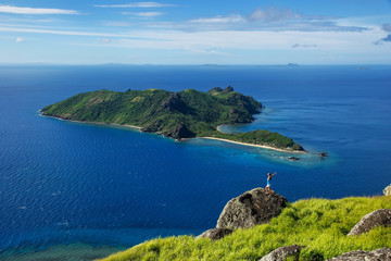 View of Kuata Island from Wayaseva Island with a hiker standing on a rock, Yasawas, Fiji
