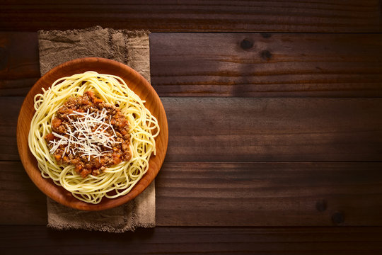 Spaghetti with homemade bolognese sauce made of fresh tomato, mincemeat, onion, garlic and carrot, photographed overhead on dark wood with natural light
