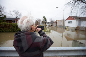 A resident takes a photo of his home after having been evacuated late last night in Sainte-Marthe-sur-le-Lac, Quebec