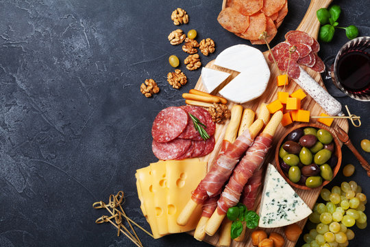 Italian appetizers or antipasto set with gourmet food on black kitchen table top view. Mixed delicatessen of cheese and meat snacks with red wine.