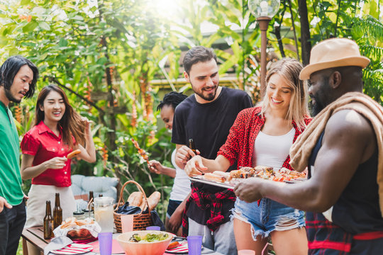 Group of diversity people having barbecue/barbeque party at home, cooking grilled meat/beef for lunch, happy friends party lifestyle concept