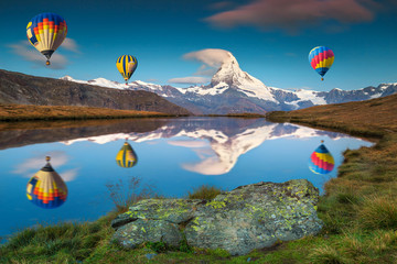 Wall Mural - Amazing Matterhorn peak and hot air balloons reflecting in water