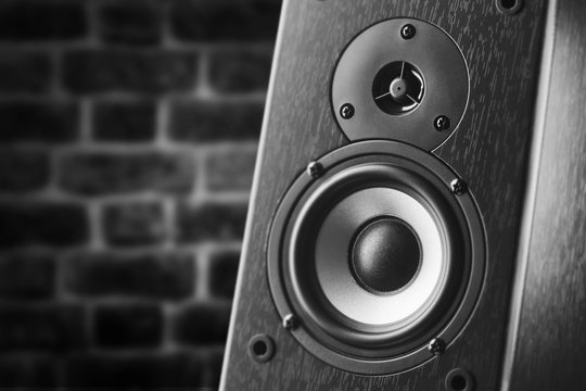 Dark color music speakers. Loud listening music. Music column on the background of a brick wall.