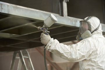 A man in a white uniform applies paint with a spray gun on a metal product.