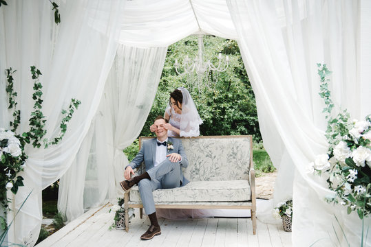 Wedding. The bride and groom are sitting on a beautiful couch in a gazebo in the garden. The bride in a pink dress, the groom in a gray suit. White tent. The bride and groom are walking in the forest.