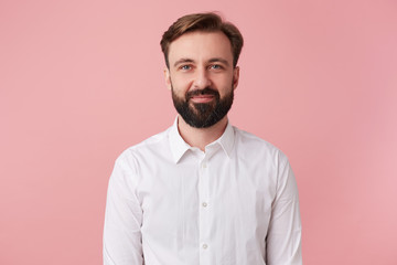 Portrait of young calm smiling handsome bearded man, wearing a white shirt. Looking at the camera isolated over pink background. Wall mural