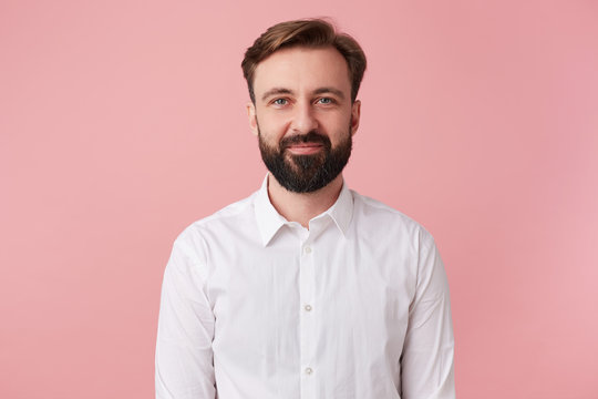 Portrait of young calm smiling handsome bearded man, wearing a white shirt. Looking at the camera isolated over pink background.