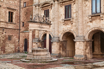 Montepulciano, Siena, Tuscany, Italy: the ancient Griffin and Lion Well (1520) in a corner of the main square
