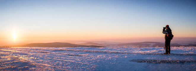 Man in winter clothes and covered his face, standing at the right of panoramic picture of landscape with hills bathed in the glow of sunset. Focus on the man's figure,background slightly out of focus.