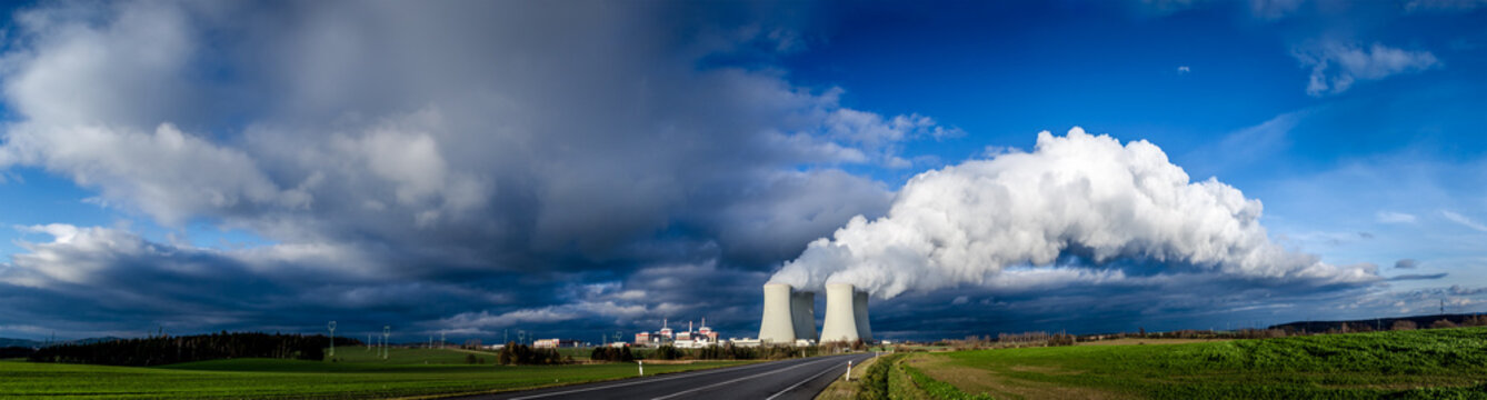 Nuclear plant and its cooling towers releasing a huge cloud of steam to the sky. Verdant vegetation around.