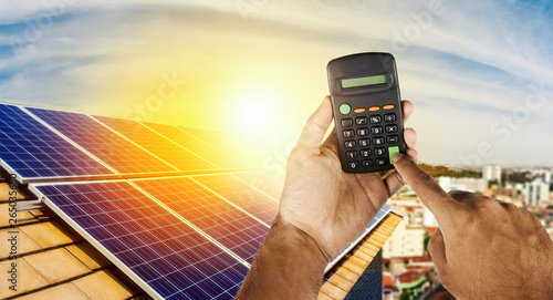 Holding a calculator on a solar panel photovoltaic