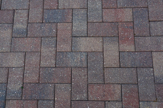 Brick paver background in a herringbone pattern with red, grey, and tan color tones.