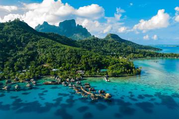 Bora Bora aerial drone video of travel vacation paradise with overwater bungalows luxury resort, coral reef lagoon ocean beach. Mount Otemanu, Bora Bora, French Polynesia, Tahiti, South Pacific Ocean