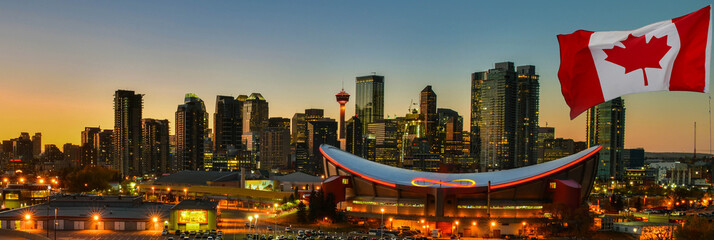 Tuinposter Canada Canadian flag in front of view Calgary city skyline at twilight time, Alberta,Canada