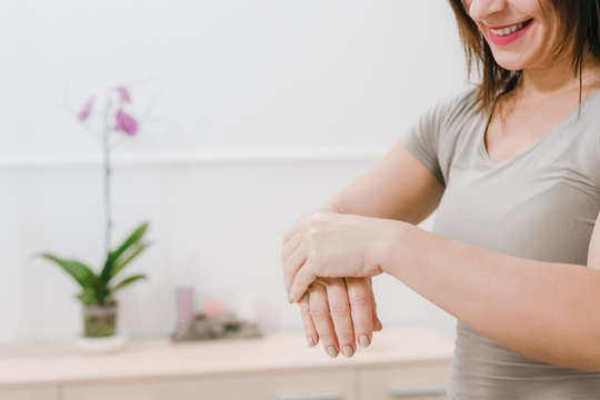 Closeup photo of female masseur stretching hands on the background of modern office