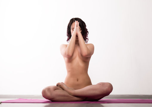 young athletic woman doing exercises on a light background. Sexy Nude yoga