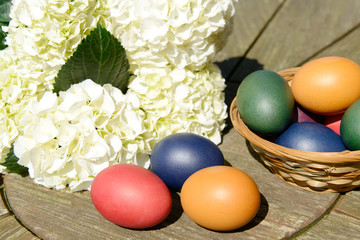 Easter eggs eggs in the basket standing on table in the garden