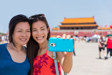 Wall Mural - Mother daughter tourists taking travel holiday selfie at Tiananmen Square Beijing, China, Asia. Smiling women taking pictures together at famous Beijing landmark.