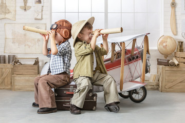 Little boys in the form of a pilot and a tourist play near the toy-plane in the room