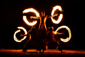 Luau Hawaii, French Polynesia fire dance silhouettes of professional dancers at night on beach...