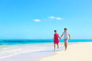 Wall Mural - Beach vacation honeymoon paradise travel destination - Young couple in love walking holding hands in idyllic holiday background.