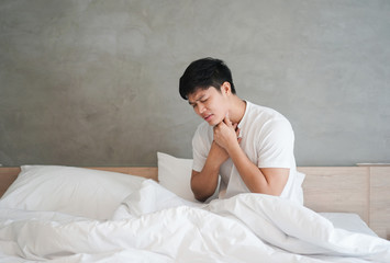 close up young asian man using hand for touching neck with feeling sore throat after wake up in the morning at bedroom , health care lifestyle people concept