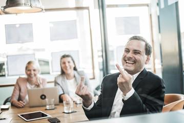 Stinkefinger im Büro bei der Besprechung
