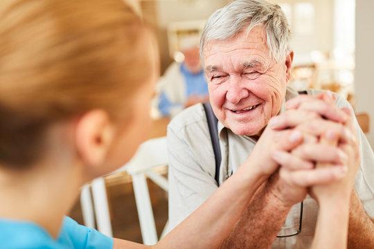 Pflegedienst tröstet Senior Mann bei Hausbesuch