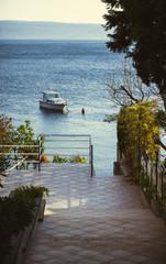Widok z tarasu na cumującą na morzu łódkę.