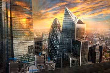 City of London, UK. Skyline view of the famous financial bank district of London at golden sunset hour. View includes skyscrapers, office buildings and beautiful sky.