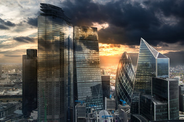 City of London, UK. Skyline view of the famous financial bank district of London at golden sunset hour. View includes skyscrapers, office buildings and beautiful sky.  Wall mural