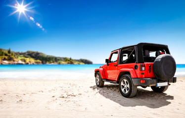 Red summer car on beach and free space for your decoration. Summer sunny day and blue sky.