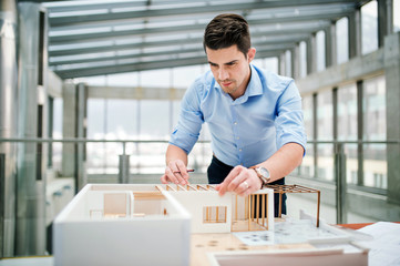 Young businessman or architect with model of a house standing in office, working.